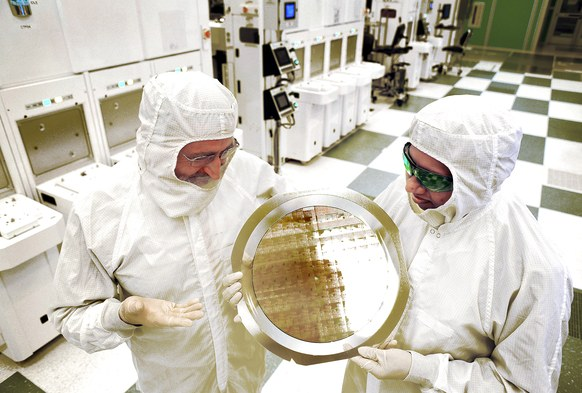 Scientists in protective clothing hold up IBM's 7 nm chip wafer